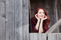 Girl near a wooden wall. Royalty Free Stock Photography