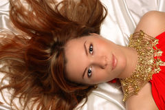 Girl with necklace. Beautiful girl with necklace lie on white cloth Stock Photo