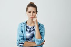 Girl need to find answer. Charming young caucasian woman with bun hairstyle holding fingers on cheek and chin, looking. Seriously and troubled at camera Stock Photos