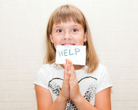 Girl needs help. Little girl shows sign card with help message Royalty Free Stock Photos