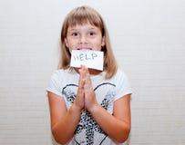 Girl needs help. Praing with card in teeth Stock Photos