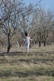 Girl in white running along old almond garden Royalty Free Stock Image