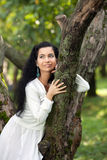 The girl nestles on a tree Stock Image