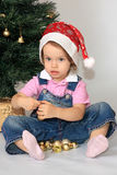 A girl is in a new-year cap. A little girl in the cap of Santa Claus studies new-year toys Royalty Free Stock Photography