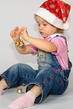 A girl is in a new-year cap. A little girl in the cap of Santa Claus studies new-year toys Stock Images