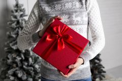 The girl in a New Year`s sweater with deer holds in hand a red box with a gift and a red tape against the background of a fir-tree royalty free stock photo
