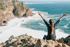 The girl next to the Atlantic Ocean in Portugal raises up her hands shows how pleased she is royalty free stock photos