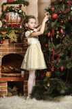 Girl next to a Christmas tree Stock Images