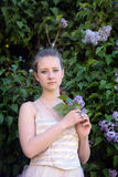 Girl next to a flowering lilac Stock Image