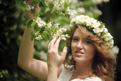 Girl next to a flowering tree Royalty Free Stock Photo