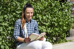 Girl in a plaid shirt sitting with a book about a green Bush and smiles. Girl next to green Bush sits with a book in hand and smiling royalty free stock image