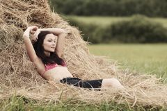 Girl next to haystack Stock Photos