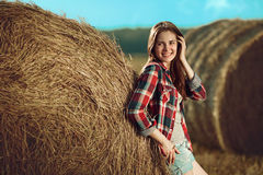 Girl next to haystack Stock Images