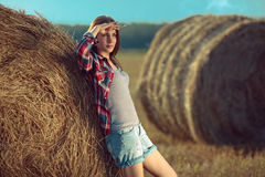 Girl next to a haystack Royalty Free Stock Image