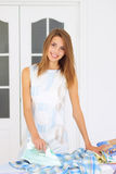 Girl next to ironing board. Beautiful girl next to ironing board Royalty Free Stock Photography