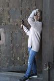 Girl next to an old wooden door. Stock Photos