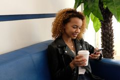 A beautiful young modern black woman, in a leather jacket with airpods in her ear, sits on a blue sofa. The girl next to royalty free stock photos