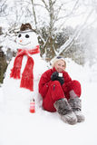 Girl Next To Snowman With Hot Drink Stock Photo