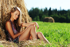 Girl next to a stack of hay Royalty Free Stock Images