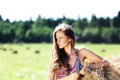 Girl next to a stack of hay Royalty Free Stock Photography