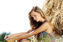 Girl next to a stack of hay Royalty Free Stock Image