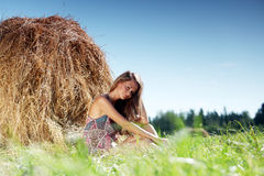 Girl next to a stack of hay Stock Images