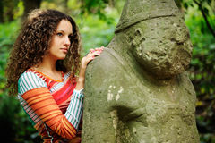 The girl next to a stone idol Stock Photography