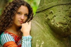 The girl next to a stone idol Stock Images