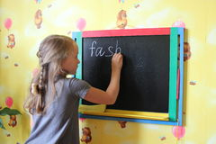 Girl with nice plaits writes Fashion on blackboard Stock Photography
