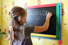 Girl with nice plaits writes Fashion on blackboard Stock Photo