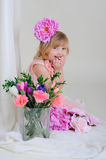 Girl with nice teeth blesyatschimi eyes flower in her hair and a. Pink dress and laughs and lightly covers her mouth half-bent fingers Stock Images