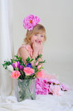 Girl with nice teeth blesyatschimi eyes flower in her hair and a. Pink dress laughs and points a finger at mouth Stock Photography