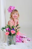 Girl with nice teeth blesyatschimi eyes flower in her hair and a. Pink dress laughs and points a finger at mouth Royalty Free Stock Photos