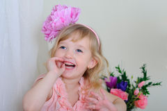 Girl with nice teeth flower in her hair and a pink dress laughin. Girl with nice teeth blesyatschimi eyes flower in her hair and a pink dress laughing Stock Photo