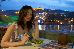 Girl, night, dinner at an outdoor cafe. Smiling woman seating in restaurant outside near riverfront royalty free stock photo