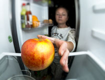 Girl night out of the fridge pulls out an Apple. Hungry woman eating at night near refrigerator Stock Photos