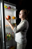 Girl night out of the fridge pulls out an Apple. Hungry woman eating at night near refrigerator Royalty Free Stock Images