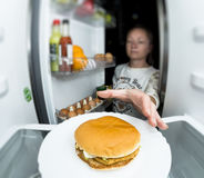 Girl night out of the fridge takes a sandwich. Hungry woman eating at night near refrigerator Stock Photography
