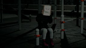 Girl at night wearing a box with an unhappy face drawing on her head. Concept of sorrow and unhappiness. 4K UHD 60 to. Girl at night wearing a box with an stock footage