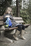 Girl with no friends. Little girl coming from school sitting lonely at a bench outdoors. Bullied or depressed child Stock Photo