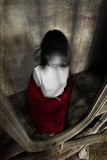 Girl with no visible face in grunge interior Stock Photo