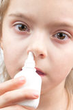 Girl with nose spray Stock Images