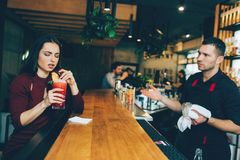A girl that is not satisfied with the cocktail that barman has made for her. She looks dissapointed. But barman looks. Sad as well because he doesn`t agree with Royalty Free Stock Photo