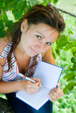 Girl with notebook. Young girl is writing in her notebook Royalty Free Stock Images