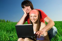 Girl with notebook and with boy on grass Stock Photography