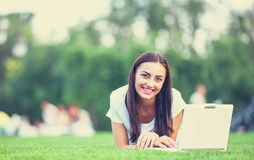 Girl with notebook. Brunette girl with notebook on green grass in the park Stock Photo