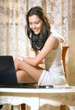 Girl with notebook computer at home Stock Photography