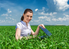 Girl with notebook on green field Royalty Free Stock Photography