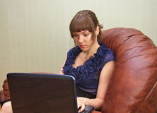 girl with a notebook on a leather sofa Stock Photo