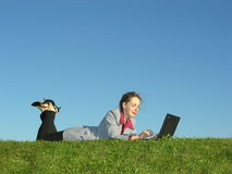 Girl with notebook lies. On green grass royalty free stock photography